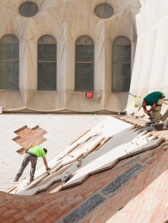 hard hats: Barcelona - 9 October 2015: Workers in hard hats laid tile on the roof of the temple of the Holy Family redemptive October 9, 2015, Barcelona, Spain