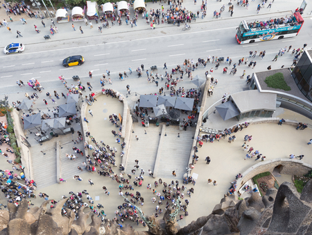 lia: Barcelona - 9 October 2015: A lot of people are standing in front of the temple of the Sagrada Familia. View down from the tower of the Nativity facade of October 9, 2015, Barcelona, Catalonia, Spain