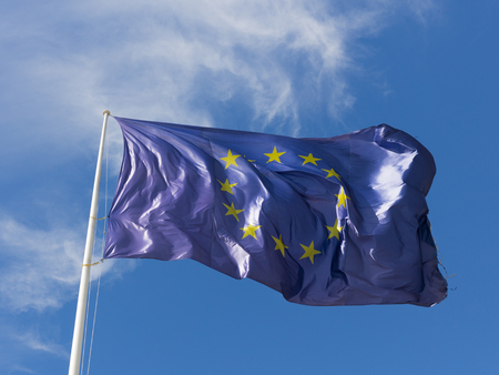 unified: dark blue with yellow stars in a circle, the flag of the EU develops on the background of blue sky and illuminated by sunlight Stock Photo