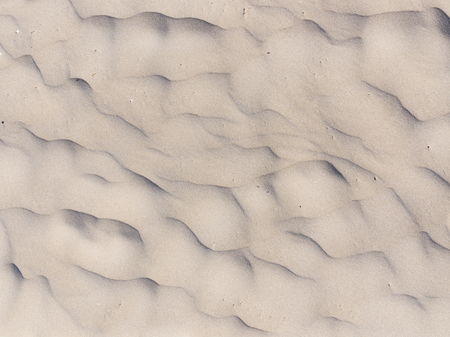 a faction: wavy fragile surface of light yellow sand fines on the beach Stock Photo