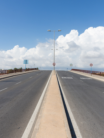restricting: four-lane asphalt road with lampposts in the middle goes beyond the horizon with blue sky and white clouds and road signs restricting speed
