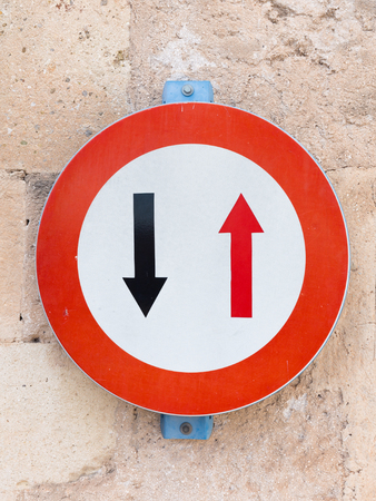 multidirectional: road sign - black and red multi-directional arrows on a white background in red circle hanging on an old stone wall Stock Photo