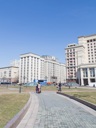 duma: Moscow - April 12 2015: View of the building of the State Duma of the Russian Federation to the Manezh Square and people walking in the spring of April 12, 2015, Moscow, Russia