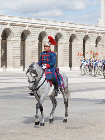Madrid - 7 October 2015: Changing of the guard at the Royal Palace and the riders in bright form horses gallop at Armory Square October 7, 2015, Madrid, Spain