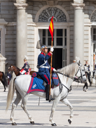 Madrid - 7 October 2015: Changing of the guard at the Royal Palace and the riders in the form of a beautiful horse galloping on the Armory Square October 7, 2015, Madrid, Spain