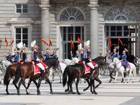 Madrid - 7 October 2015: Changing of the guard at the Royal Palace and the riders on horses galloping beautiful variegated Armory Square on October 7, 2015, Madrid, Spain