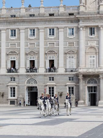Madrid - 7 October 2015: Changing of the guard at the Royal Palace and the riders on white horses gallop over the area October 7, 2015, Madrid, Spain