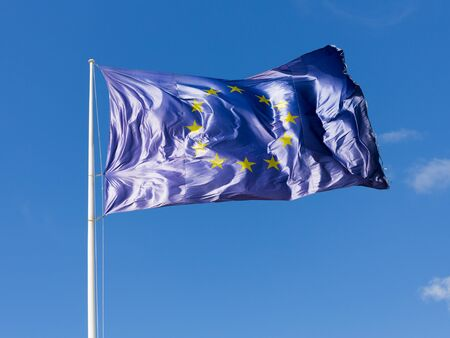 unified: blue with yellow stars in a circle, the flag of the EU develops on the background of blue sky and illuminated by sunlight