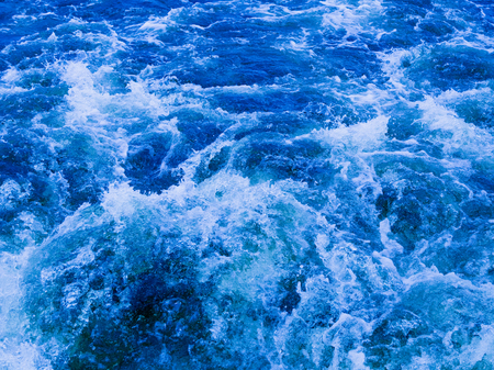 seething: a powerful stream of beautiful blue clean water flowing bubbling and splashing splashing splashes and drops in different directions and forms a foam