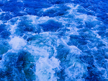 seething: Blue water flowing bubbling and splashing splashing splashes and drops in different directions and forms a white foam