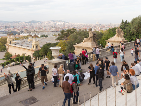 far away look: Barcelona - October 11, 2015: A lot of people look down on the beautiful Barcelona with Montjuic and Sagrada Familia is visible far away October 11, 2015 Barcelona, Catalonia, Spain