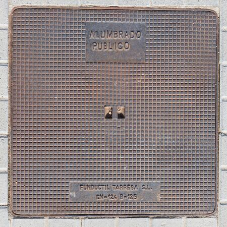 manhole cover: Madrid - October 11, 2015: Beautiful heavy metal manhole cover with a picture in a cage on the road October 11 Madrid, Spain