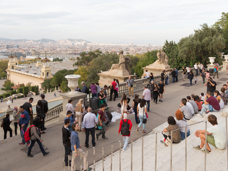 far away look: Barcelona - October 11, 2015: People look down on the beautiful Barcelona with Montjuic and Sagrada Familia is visible far away October 11, 2015 Barcelona, Catalonia, Spain