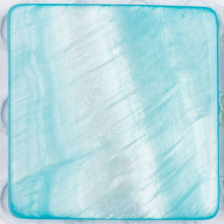 inclusions: beautiful natural light with iridescent nacre pearl shimmering in the form of a square plate for mosaics, painted in blue color Stock Photo
