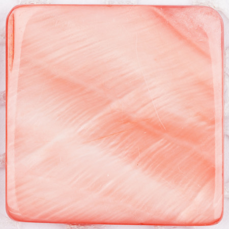 pink pearl: natural pink pearl colored with iridescent tints and inclusions in the form of a square plate for mosaic Stock Photo