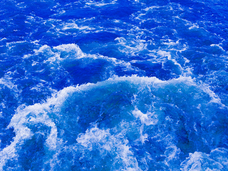 seething: a powerful stream of water flowing blue bubbling and splashing splashing splashes and drops in different directions and forms a white foam Stock Photo