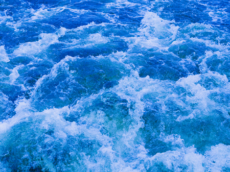 a powerful stream of beautiful blue clean water flowing bubbling and splashing splashing splashes and drops in different directions and forms a white foam
