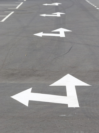 road marking: bright white arrow road marking on gray asphalt road road goes into the distance