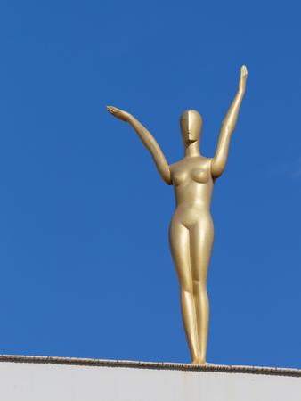 salvador dali: Figueres - October 11, 2015: Golden female figure in the building of the theater-museum of Salvador Dali in the background of blue sky October 11, 2015 Figueres, Catalonia, Spain