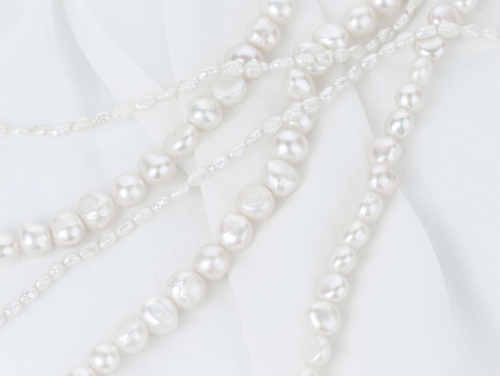 freshwater pearl: beautiful white beads made from freshwater pearls with a matte pearlescent on white cloth with folds vertically
