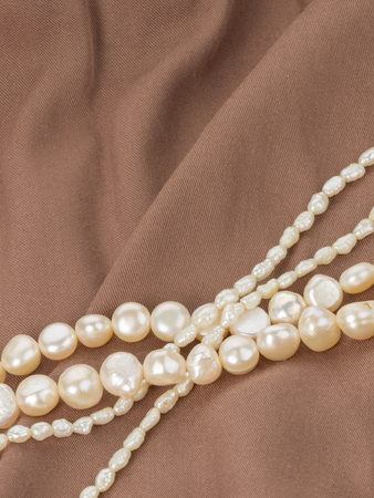 freshwater pearl: beautiful white beads made from freshwater pearls with a matte sheen on brown fabric with folds vertically