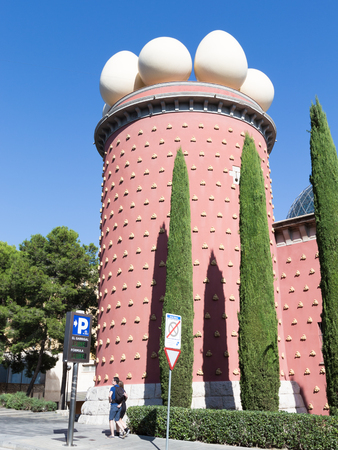 Figueres - October 11, 2015: A couple of tourists from unusual theater-museum of Salvador Dali in the background of blue sky October 11, 2015 Figueres, Catalonia, Spain Editorial