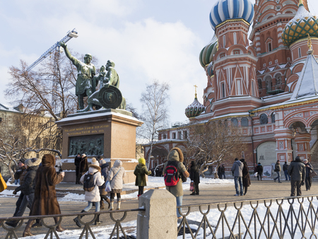 minin: Moscow - January 7, 2016: Tourists at the monument to Minin and Pozharsky on Red Square and St. Basils Cathedral January 7, 2016, Moscow, Russia
