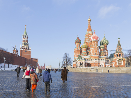 spassky: Moscow - January 7, 2016: Bright unusual multicolored domes of the ancient St. Basils Cathedral on Red Square, and many tourists go to Red Square on Jan. 7, 2016, Moscow, Russia Editorial