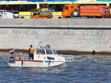 policing: Moscow - May 7, 2015: A small patrol boat with Russian flag and police moving along the Moscow River to preserve order May 7, 2015, Moscow, Russia