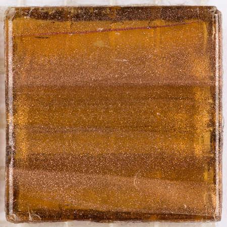aventurine: beautiful glossy square glass mosaic with light brown stripes blurred and Aventurine