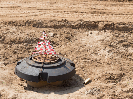 protectors: new manhole on the new road with light yellow sand fines on the construction site and traces of protectors of wheels