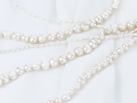 freshwater pearl: beautiful white beads made from freshwater pearls of various sizes with a matte pearlescent white on thin fabric with folds vertically