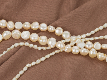 freshwater pearl: beautiful white beads made from freshwater pearls with a matte sheen on brown fabric with pleats Stock Photo