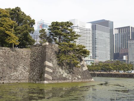 impregnable: Tokyo - January 27, 2015: The wall of gray stone of the Imperial Palace in Chiyoda district and modern tall buildings in the city center January 27, 2015, Tokyo, Japan