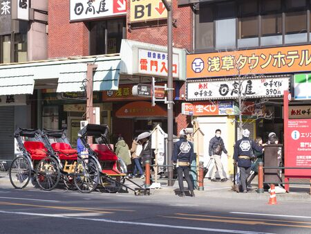 beckoning: Tokyo - February 4, 1015: Young pedicabs beckoning tourists to ride on the main street of Tokyo, February 4, 2015, Tokyo, Japan