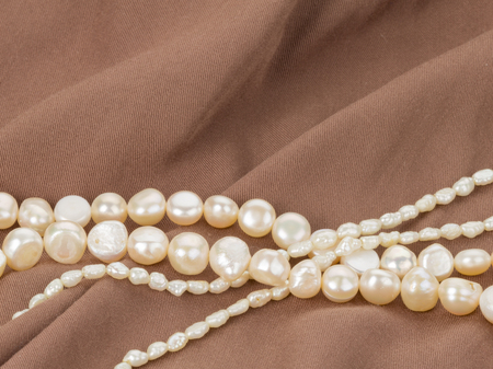 freshwater pearl: beautiful white beads made from freshwater pearls on brown fabric with pleats