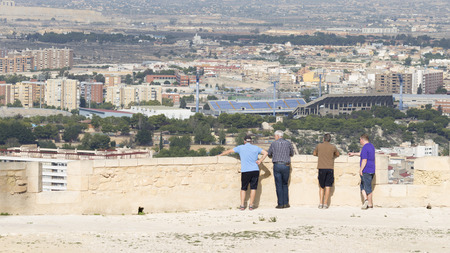 far away look: Alicante - 4 October 2015: People admire the surroundings of the tourist city of Alicante from castle Santa Barbara, October 4, 2015, Alicante, Spain