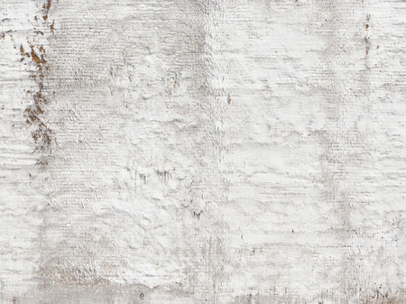 smudges: uneven surface of an old white wall, painted bright white with peeling paint and rusty smudges shabby spots