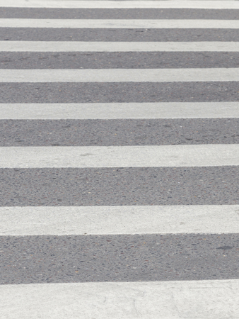 inclusions: abstraction with crosswalk with white horizontal stripes on a gray old pavement with inclusions of gravel on the road near that clear and up blurred