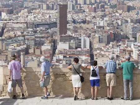 far away look: Alicante - 4 October 2015: Tourists admiring the surroundings of the tourist city of Alicante from castle Santa Barbara, October 4, 2015, Alicante, Spain