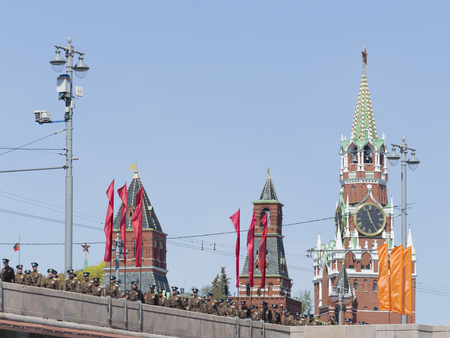 spassky: Moscow - May 7th, 2015: Beautiful Kremlins Spassky Tower clock - chimes, red flags and soldiers and officers are in uniform after a rehearsal of the parade on Red Square on May 7, 2015, Moscow, Russia