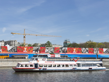 spassky: Moscow - May 7, 2015: A passenger pleasure boat Moscow-21 floats on the river against the background of Mokwa crossing the promenade decorated soldiers and foitserov Victory Parade rehearsal on May 7th, 2015, Moscow, Russia