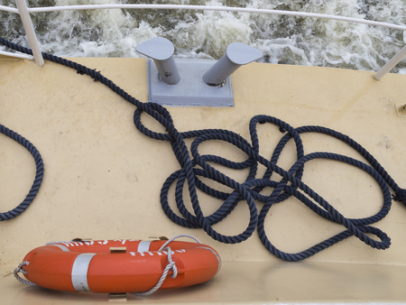 rages: blue old torn rope lying on the deck of an old yellow light, bright lifebuoy hanging and waves pleschatsya zabortom while moving ship Stock Photo