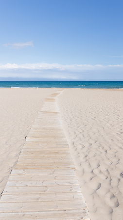 good weather: Light wooden walkway through the city sandy beach leads to the calm blue sea at night in good weather Alicante, Costa Blanca, Spain