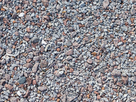 brown granite: small gray and brown granite gravel rubble in the street Stock Photo