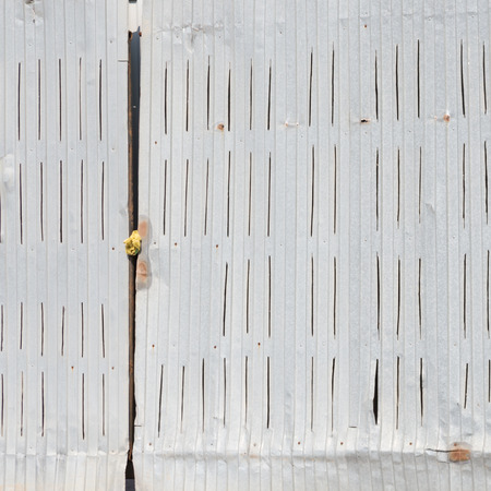 slits: old gray metal gates of crumpled gofrolist with vertical slits in the convex parts
