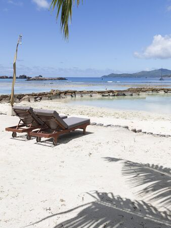east africa: Lovely bright seascape with clean white sand and clear blue sea, tropical greenery and two loungers on the beach in the Seychelles, East Africa
