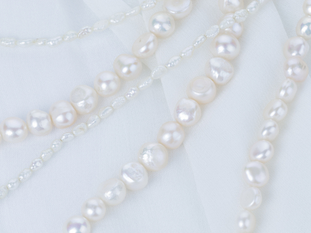 freshwater pearl: beautiful white beads made from freshwater pearls of various sizes with a matte pearlescent on white cloth with folds vertically