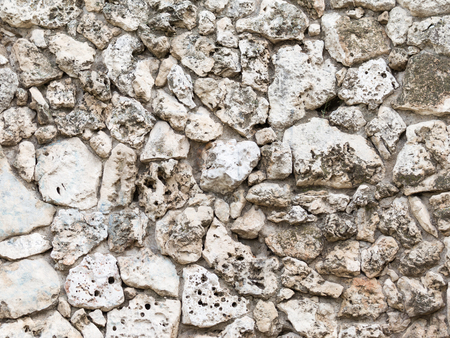 porous brick: stone wall of old natural beige and gray tuff rough fractured surfaces and porous structure