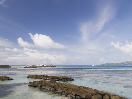 east africa: Lovely bright seascape with a breakwater of natural stones in a clean transparent blue sea and beautiful white clouds in the blue sky reflected in the water, Seychelles, East Africa Stock Photo